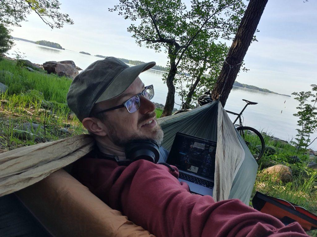 CTO Jaakko Alajoki riippumatossa etätyöpisteensä äärellä - järvenrannalla. Ottaa selfien.